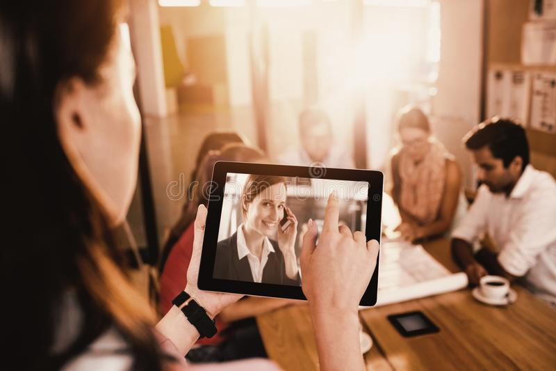 Sammansatt bild av affärskvinnan som använder den digitala minnestavlan, medan diskutera med kollegor arkivfoto