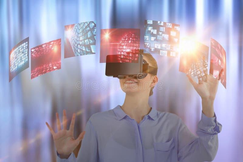 Sammansatt bild av affärskvinnan som erfar virtuell verklighet royaltyfria bilder
