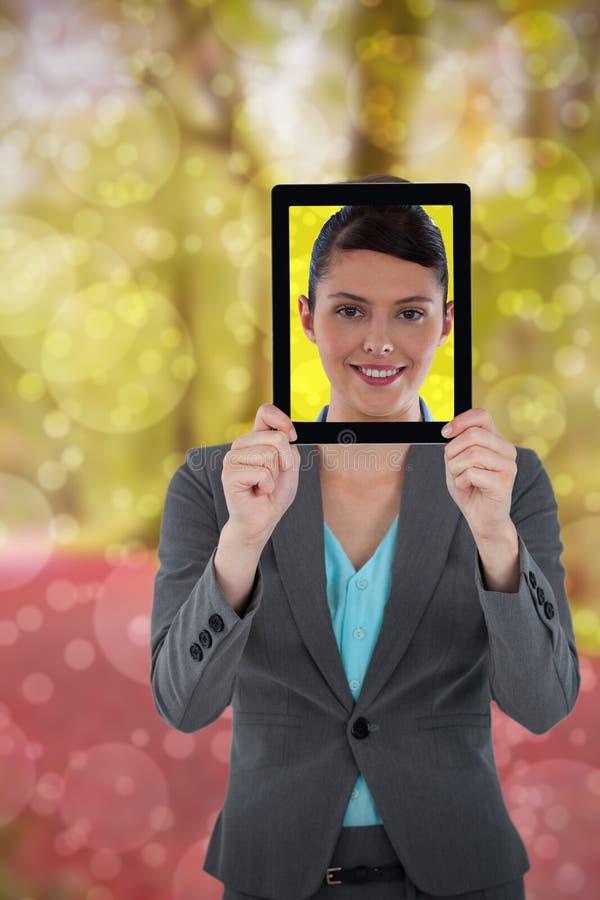 Sammansatt bild av affärskvinnan som rymmer den digitala minnestavlan royaltyfria bilder