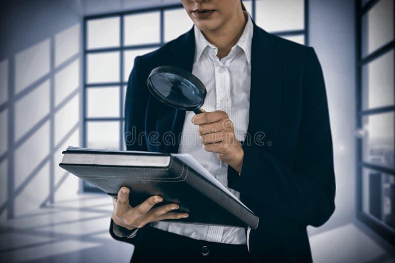 Sammansatt bild av affärskvinnan som ser dokumentet till och med förstoringsglaset royaltyfri foto