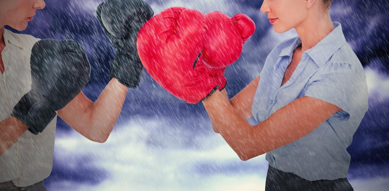 Sammansatt bild av affärskvinnor med att slåss för boxninghandskar arkivbilder