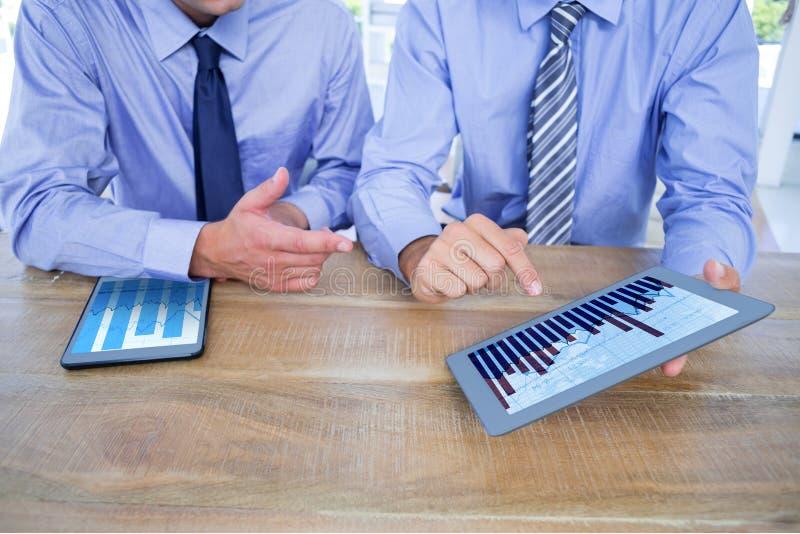 Sammansatt bild av affärsmän som använder den digitala minnestavlan på tabellen royaltyfri bild