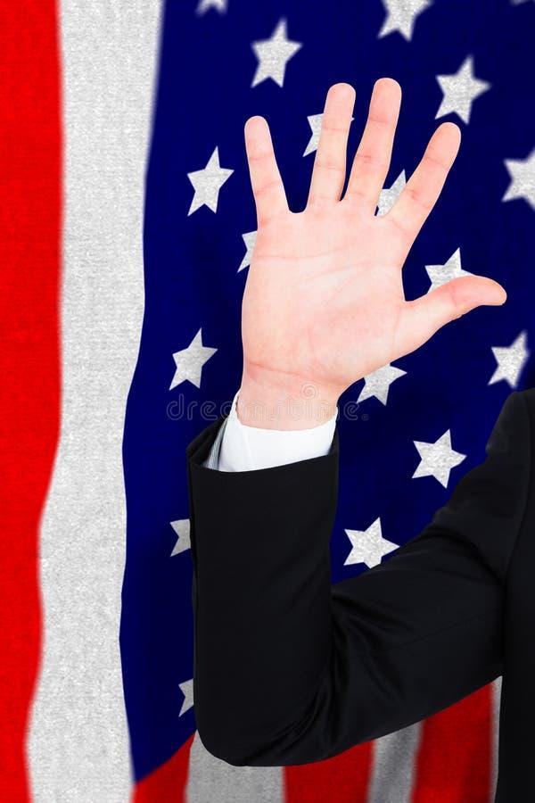 Sammansatt bild av affärsmannen i dräkt med den lyftta handen royaltyfri bild
