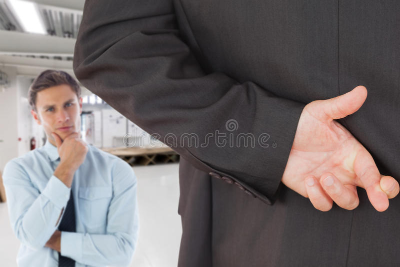 Sammansatt bild av affärsmannen med korsade fingrar arkivbild