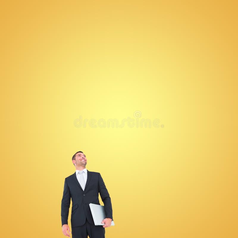 Sammansatt bild av affärsmannen som ser som rymmer upp bärbara datorn royaltyfri fotografi