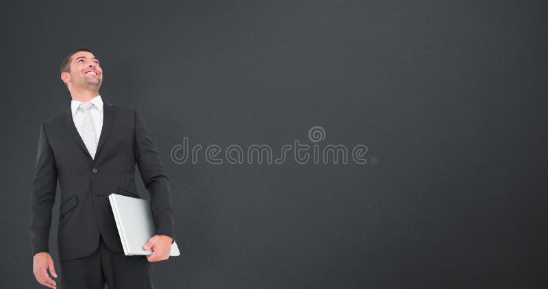 Sammansatt bild av affärsmannen som ser som rymmer upp bärbara datorn arkivfoto