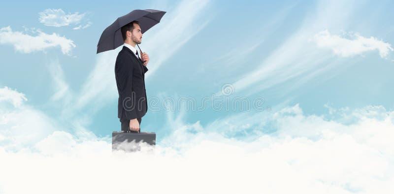 Sammansatt bild av aff?rsmannen under paraplyet, medan rymma en portf?lj arkivfoto