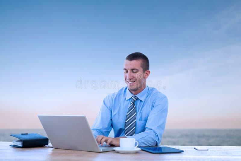 Sammansatt bild av att le affärsmannen som arbetar med hans bärbar dator fotografering för bildbyråer