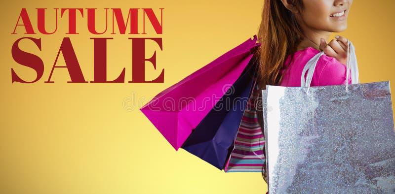 Sammansatt bild av att le den asiatiska kvinnan med shoppingpåsar royaltyfria bilder