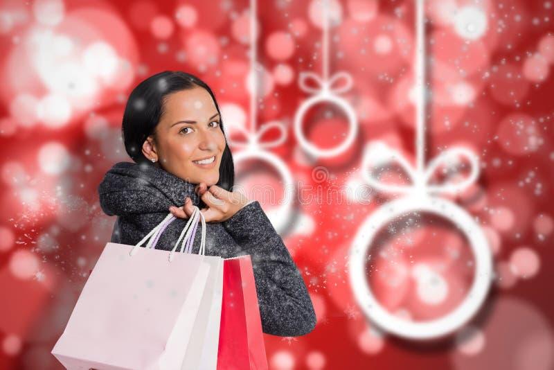 Sammansatt bild av att le den hållande shoppingpåsen för kvinna royaltyfria bilder