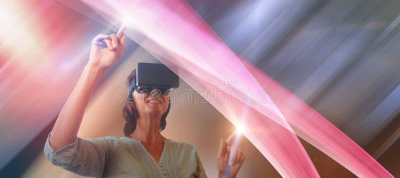Sammansatt bild av att le den mogna kvinnan som använder virtuell verklighetexponeringsglas royaltyfri bild