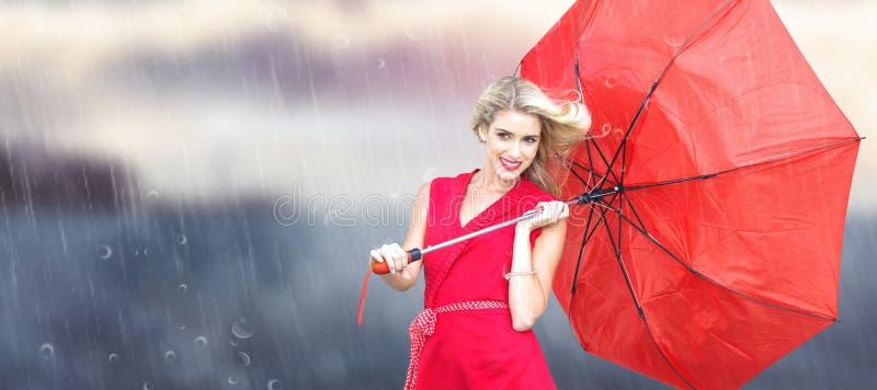 Sammansatt bild av att le det blonda hållande paraplyet royaltyfri foto