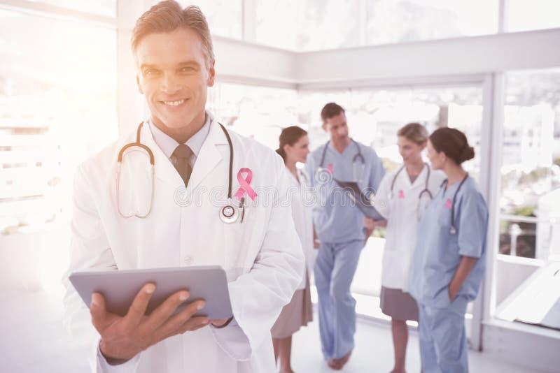 Sammansatt bild av att le doktorn som rymmer den digitala minnestavlan royaltyfri fotografi