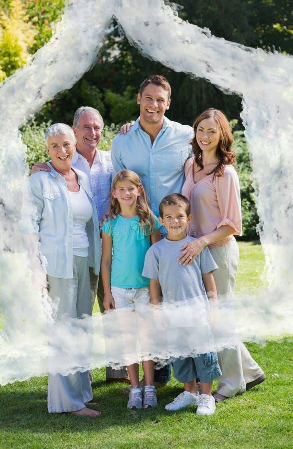 Sammansatt bild av att le familjen och morföräldrar i parkera royaltyfria foton