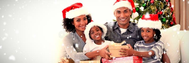 Sammansatt bild av att le familjen som delar julgåvor royaltyfri bild