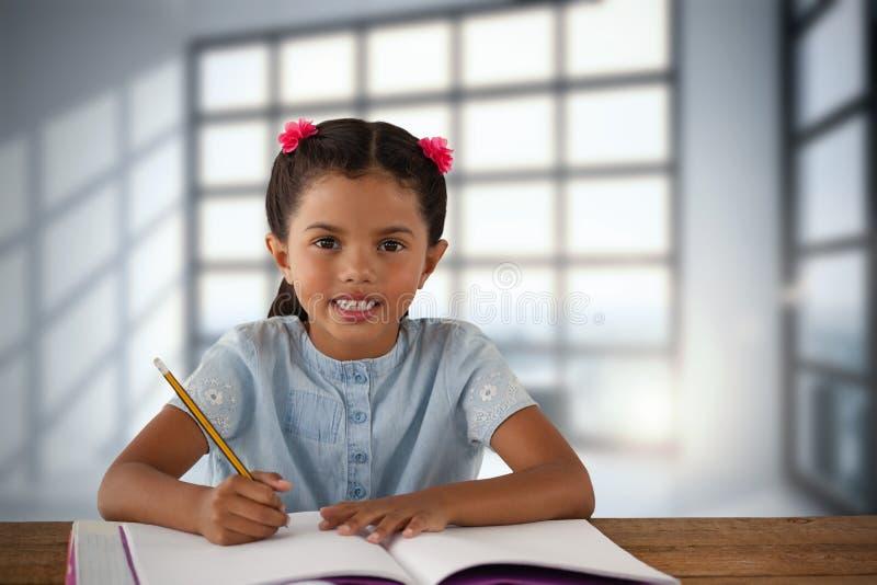 Sammansatt bild av att le flickahandstil i bok på skrivbordet royaltyfri fotografi