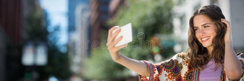 Sammansatt bild av att le flickan som tar en selfie royaltyfri foto