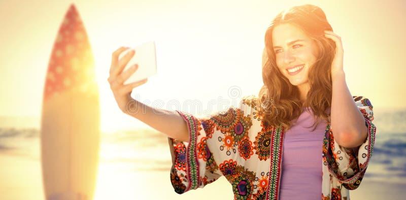 Sammansatt bild av att le flickan som tar en selfie fotografering för bildbyråer