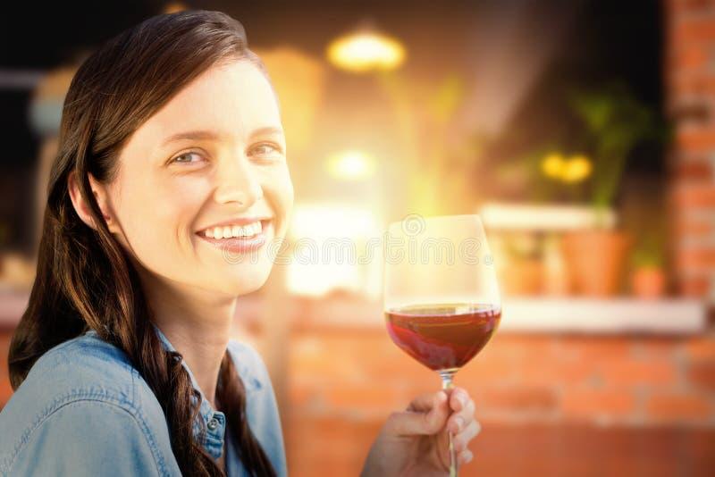 Sammansatt bild av att le kvinnan som rymmer ett exponeringsglas av rött vin royaltyfri foto
