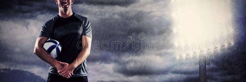 Sammansatt bild av att le rugbyspelaren i svart ärmlös tröjainnehavboll med knäppte fast händer arkivbilder