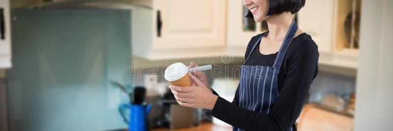 Sammansatt bild av att le servitrishandstil på den disponibla kaffekoppen royaltyfri bild