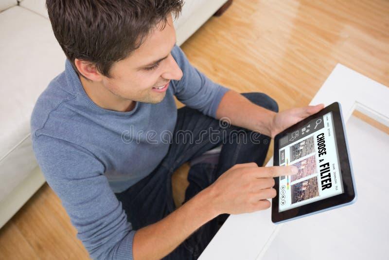 Sammansatt bild av den över huvudet sikten av mannen som använder den digitala minnestavlan i vardagsrum royaltyfria foton