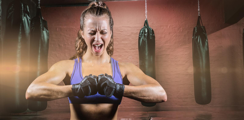 Sammansatt bild av den aggressiva kvinnliga boxaren som böjer muskler arkivbilder