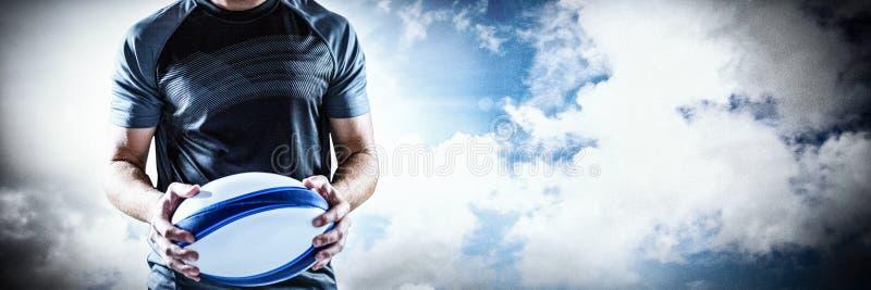 Sammansatt bild av den allvarliga bollen för rugbyspelareinnehav royaltyfri fotografi