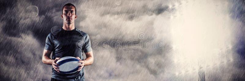 Sammansatt bild av den allvarliga rugbyspelaren i svart ärmlös tröjainnehavboll royaltyfri foto
