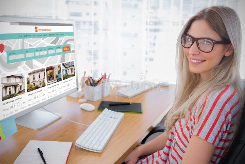 Sammansatt bild av den attraktiva fotoredaktören som arbetar på datoren royaltyfri bild