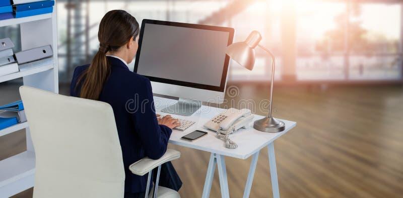 Sammansatt bild av den bakre sikten av affärskvinnan som använder datoren royaltyfria foton