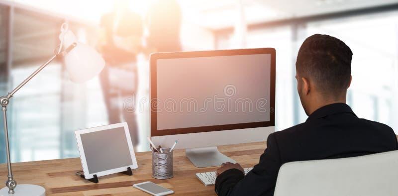 Sammansatt bild av den bakre sikten av affärsmannen som arbetar över datoren royaltyfria foton