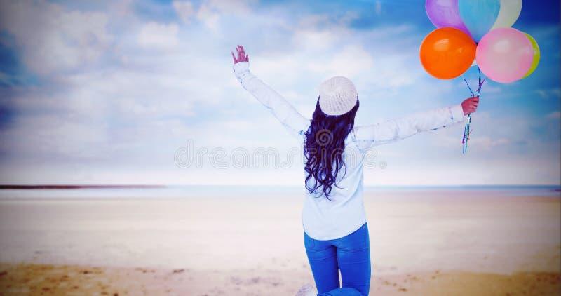 Sammansatt bild av den bakre sikten för full längd av den bekymmerslösa kvinnan som rymmer färgrika ballonger royaltyfri bild