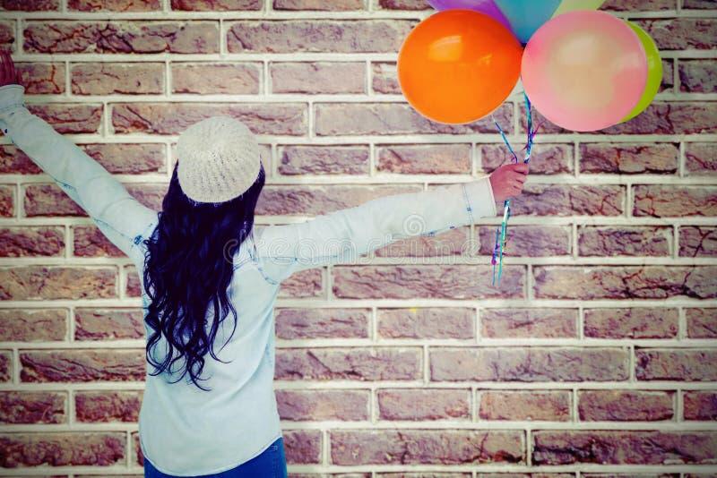 Sammansatt bild av den bakre sikten för full längd av den bekymmerslösa kvinnan som rymmer färgrika ballonger royaltyfri fotografi