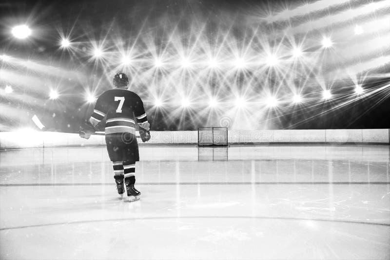 Sammansatt bild av den bakre sikten av spelaren som rymmer ishockeypinnen royaltyfri fotografi