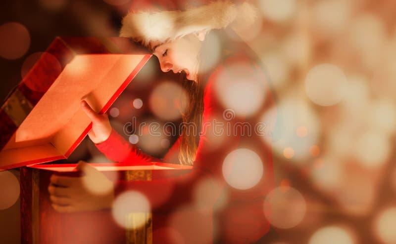 Sammansatt bild av den festliga lilla flickan som öppnar en glödande julgåva arkivfoto