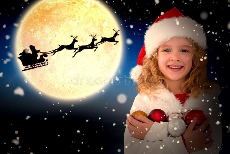 Sammansatt bild av den festliga lilla flickan som ler på kameran royaltyfria foton