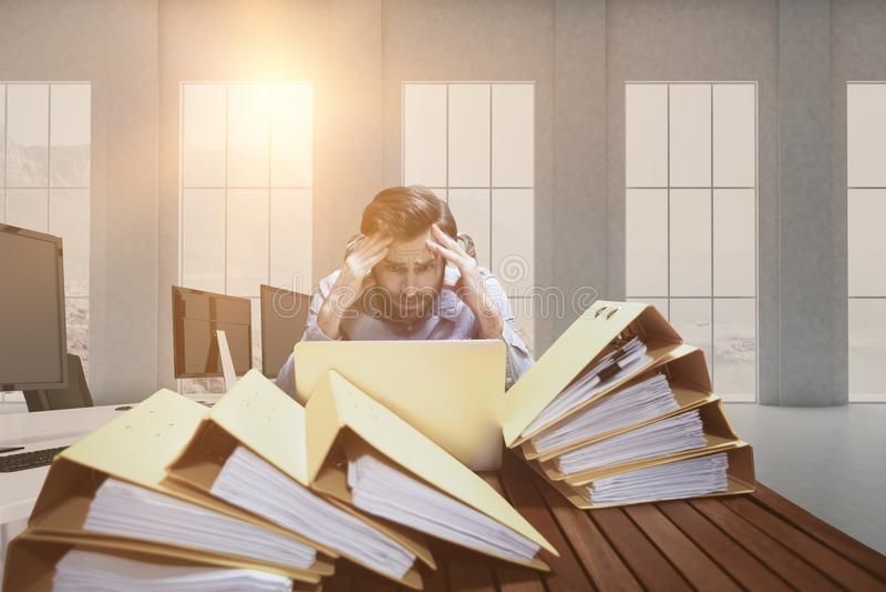 Sammansatt bild av den frustrerade affärsmannen med huvudet i händer som sitter på skrivbordet royaltyfri bild