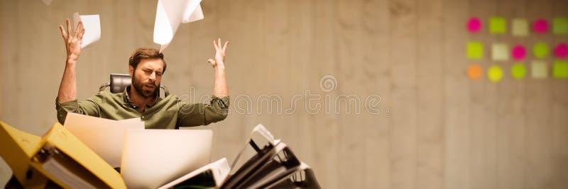 Sammansatt bild av den frustrerade affärsmannen som kastar papper, medan sitta på tabellen arkivfoton