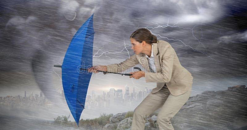 Sammansatt bild av den fulla längden av affärskvinnan som försvarar med det blåa paraplyet royaltyfria bilder
