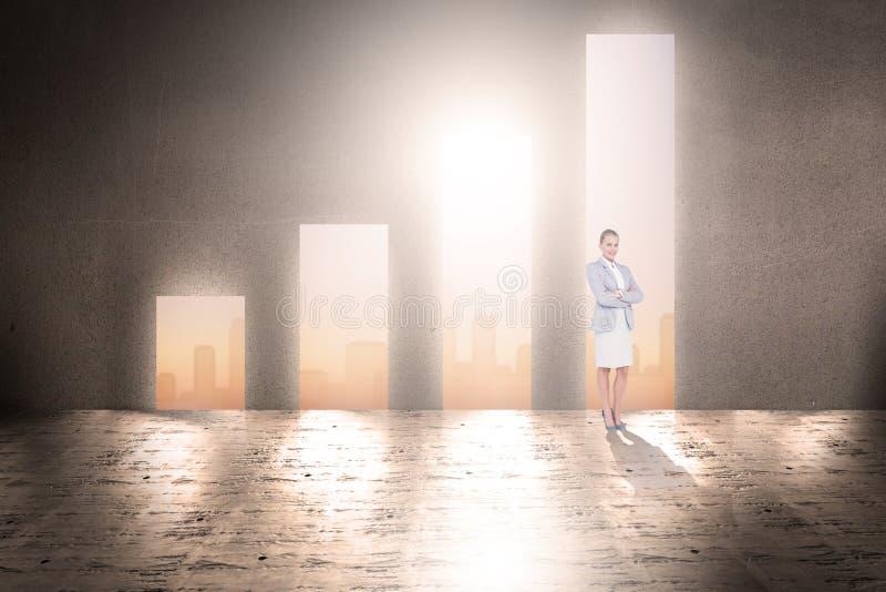 Sammansatt bild av den fulla längdståenden av en affärskvinna med korsade armar fotografering för bildbyråer