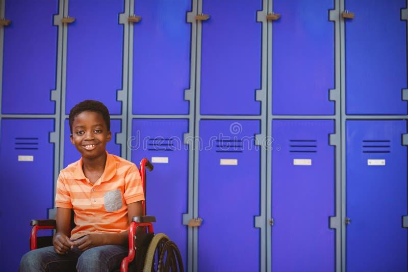 Sammansatt bild av den fulla längdståenden av den lyckliga pojken på rullstolen arkivfoton