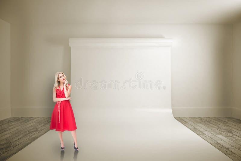 Sammansatt bild av den fundersamma blondinen som bär den röda klänningen royaltyfri fotografi