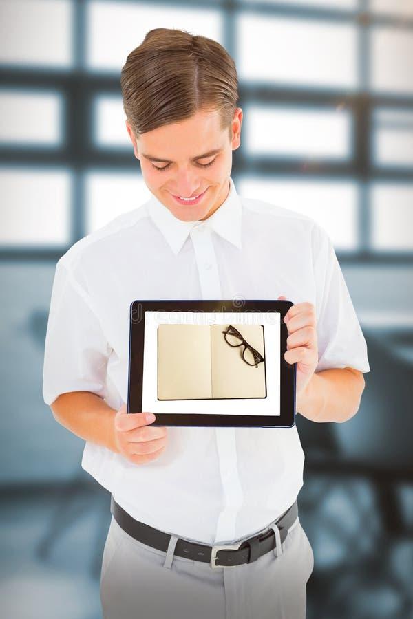 Sammansatt bild av den geeky affärsmannen som visar hans minnestavlaPC arkivfoto