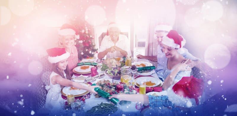 Sammansatt bild av den gladlynta familjen på att äta middag tabellen för julmatställe royaltyfri foto