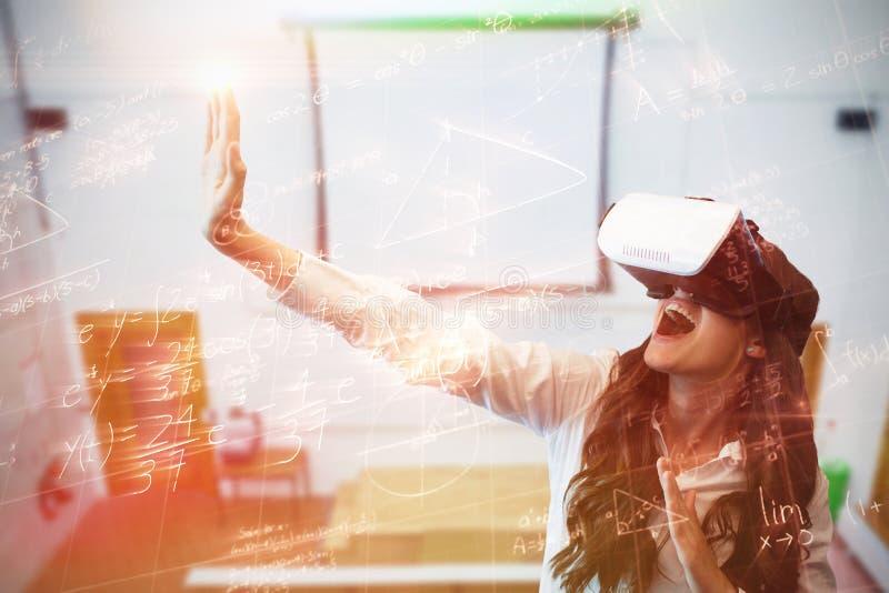 Sammansatt bild av den gladlynta kvinnan som gör en gest, medan bära virtuell verklighetexponeringsglas royaltyfria foton