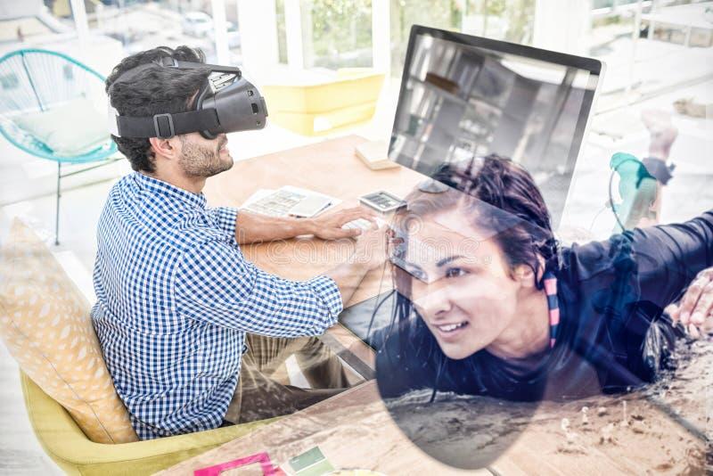 Sammansatt bild av den grafiska formgivaren i virtuell verklighetsimulator, medan genom att använda datoren royaltyfri fotografi