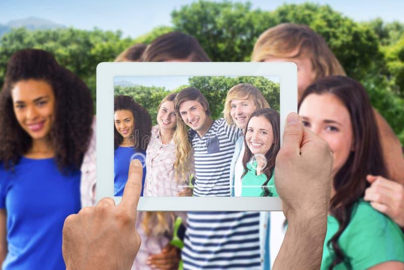 Sammansatt bild av den hållande minnestavlaPC:n för hand royaltyfria foton