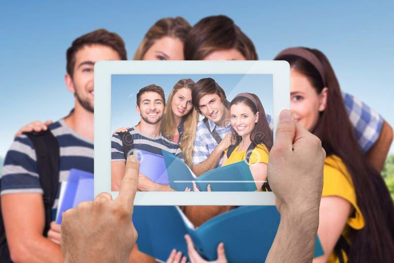 Sammansatt bild av den hållande minnestavlaPC:n för hand fotografering för bildbyråer