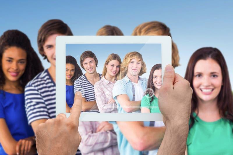 Sammansatt bild av den hållande minnestavlaPC:n för hand royaltyfri fotografi